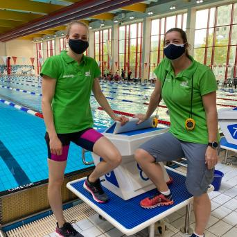 Trainerin und ihr Schützling begutachten neuen Startblock in Schwimmhalle